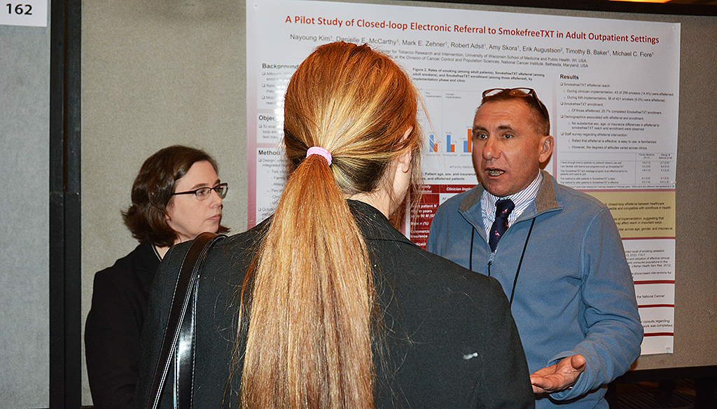 Mark Zehner (right) and UW-CTRI Associate Director of Research Dr. Danielle McCarthy (left) discuss their research with a fellowSRNT attendee.