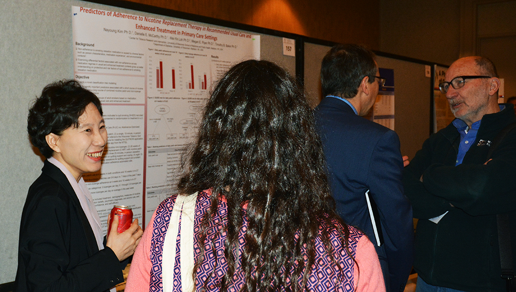 UW-CTRI Postdoctoral Research Associate Dr. Nayoung Kim (far left) discussed her research findings with several SRNT attendees. Kim presented three different posters.